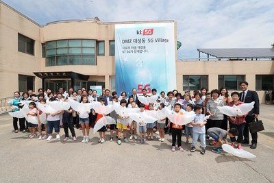 KT executives, including Chairman Hwang Chang-Gyu (center), and residents, elementary school teachers and students are pictured in front of town hall at the opening ceremony of 5G Village in the DMZ's Daeseong-dong on June 27