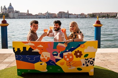 Three artists pose with their collaborative piece of urban art, a sofa celebrating Aperol's centenary and role in sparking joyful connections