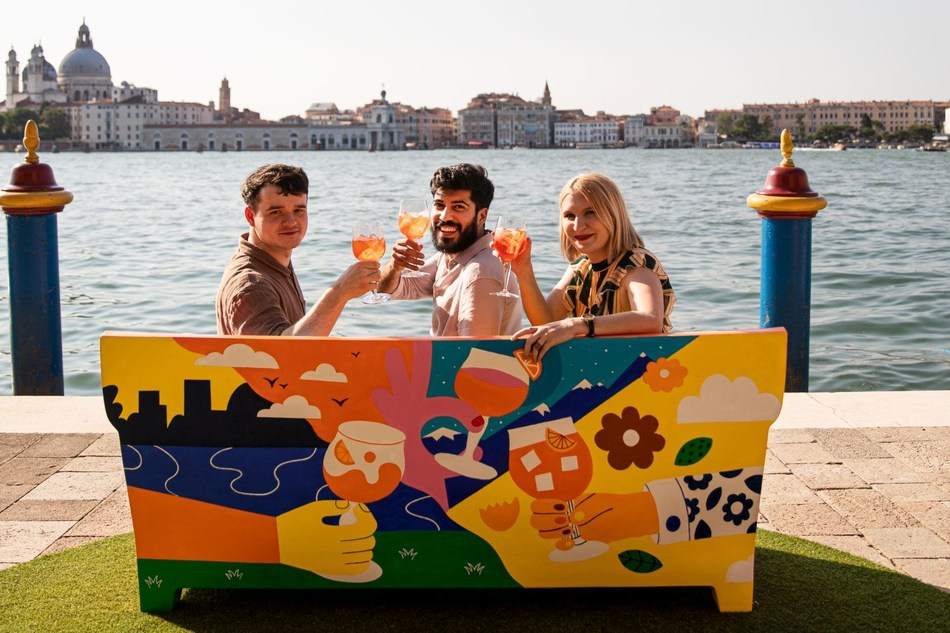 Three artists pose with their collaborative piece of urban art, a sofa celebrating Aperol's centenary and role in sparking joyful connections (PRNewsfoto/Aperol)