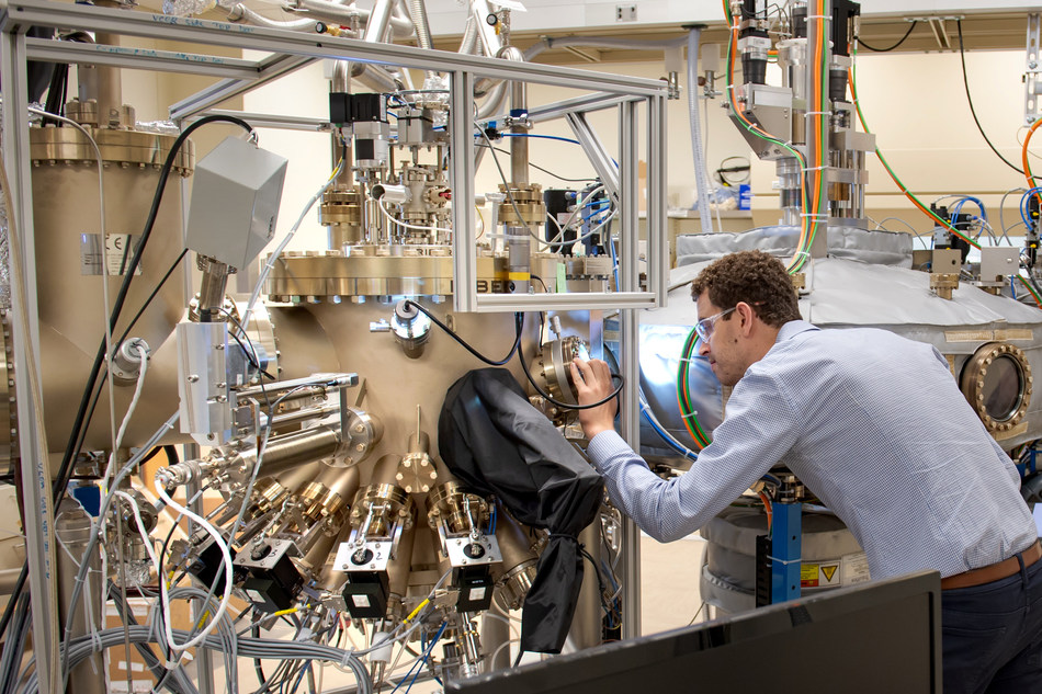 Recent University of Chicago PhD graduate Sam Whiteley examines the sample chamber of Argonne's Riber molecular beam epitaxy tool, which grows materials that host quantum defects. Sam will join Chicago Quantum Exchange corporate partner HRL Laboratories in August 2019. Photo courtesy of Argonne National Laboratory.