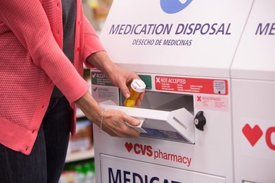 A customer disposes of unwanted prescription drugs at a CVS Pharmacy in-store safe medication disposal unit.
