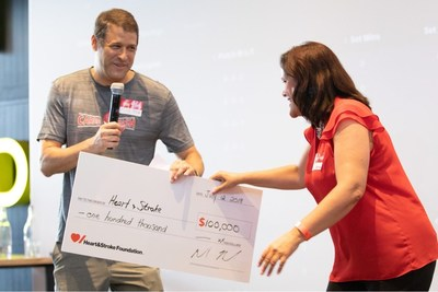 Michael Kessel, CEO of Cleveland Clinic Canada,  and the founder of Cardiac Smash hands Avril Goffredo, Executive Vice President, Ontario & Nunavut, Heart & Stroke a symbolic cheque for $100 thousand at last year's event. (CNW Group/Heart and Stroke Foundation)