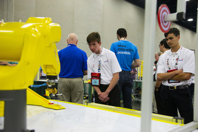 Noah Logan, left, a student at Stafford Technical Center in Rutland, Vermont, watches a FANUC robot arm place on a target the 3D Printed tool he designed with his teammate Matthew Noel, who looks on during the 2019 SkillsUSA Additive Manufacturing Competition.