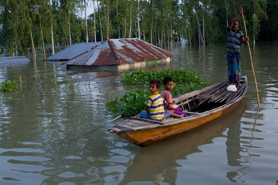 In Bangladesh, a father and his children are patrolling around their house that has submerged completely under water. © UNICEF/UN0328139/Alam Kiron/Unicef (CNW Group/UNICEF Canada)