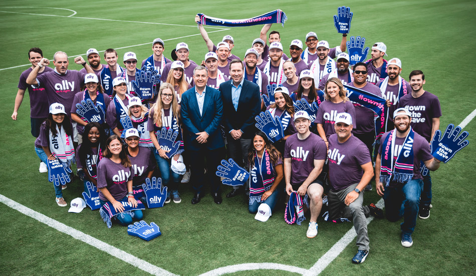 An excited group of employees gather around Ally Financial CEO, Jeffrey Brown (left) and Tom Glick (right), leader of the Charlotte Bid Team Friday after they announced a multi-year agreement. The agreement names Ally the founding and lead partner of a potential Major League Soccer team in Charlotte and the Carolinas.