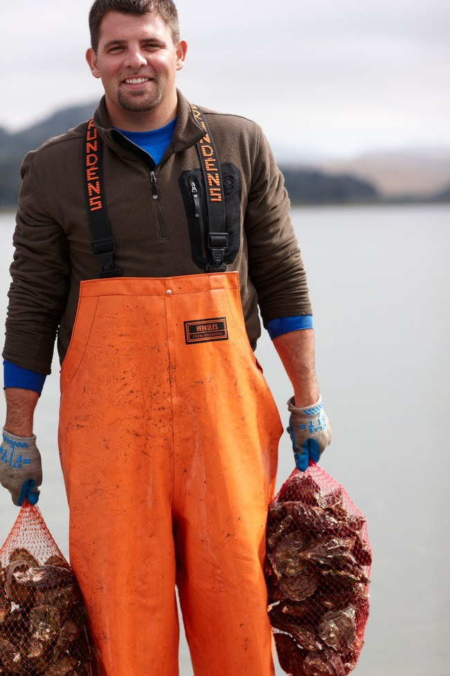 Neal Maloney, owner of Morro Bay Oyster Company, holds bags of fresh oysters.