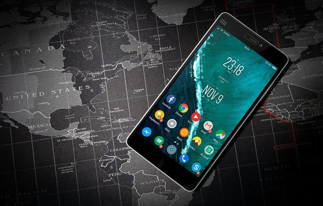 Android smartphone laying on top of a world map