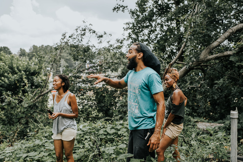 Brother Holmes leads two volunteers through the Soul Spirit Farmers garden, one of several entities active in the City of East Point's local food movement. (Photo: Caleb Jones)