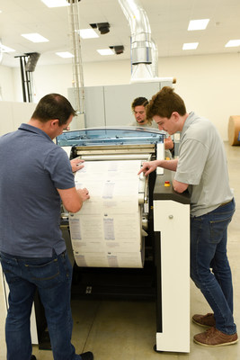Evan Liss, Ryan Newell, and David Stubee of Intellus inspecting client output from their Canon ColorStream 6900 Chroma ink jet printing system.