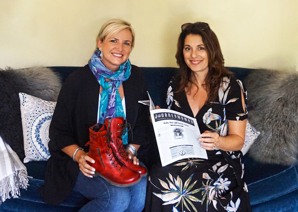 Extending the Legacy of Journeywoman: New Journeywoman CEO Carolyn Ray (left) and Erica Ehm (right), daughter of Journeywoman founder Evelyn Hannon, with Evelyn's iconic red travelling boots and the original newsletter. (CNW Group/Journeywoman)