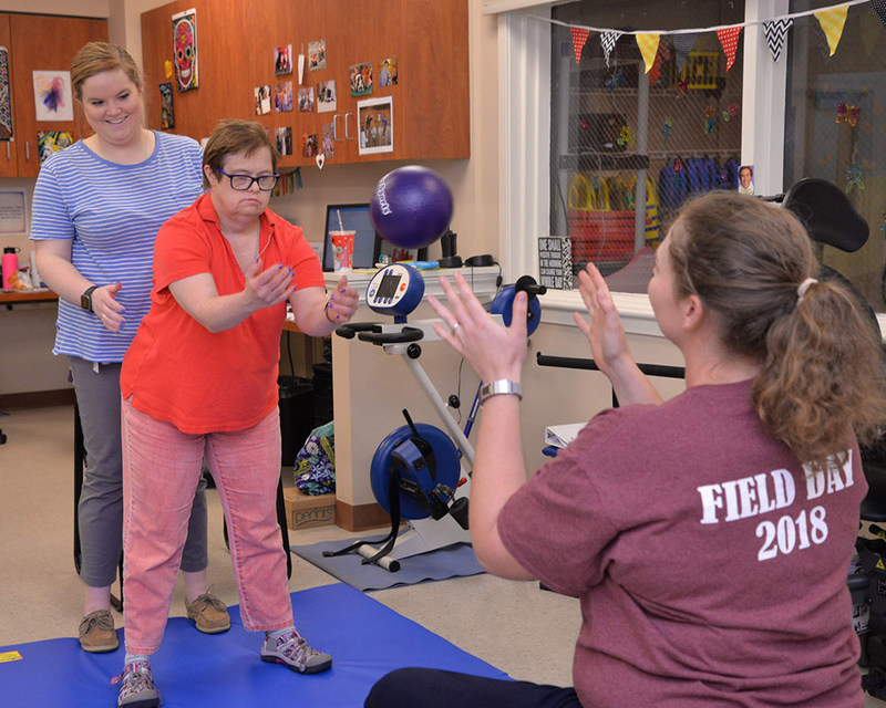 Members of Melmark's Rehabilitative Services Team working with an individual in the existing Physical Therapy space