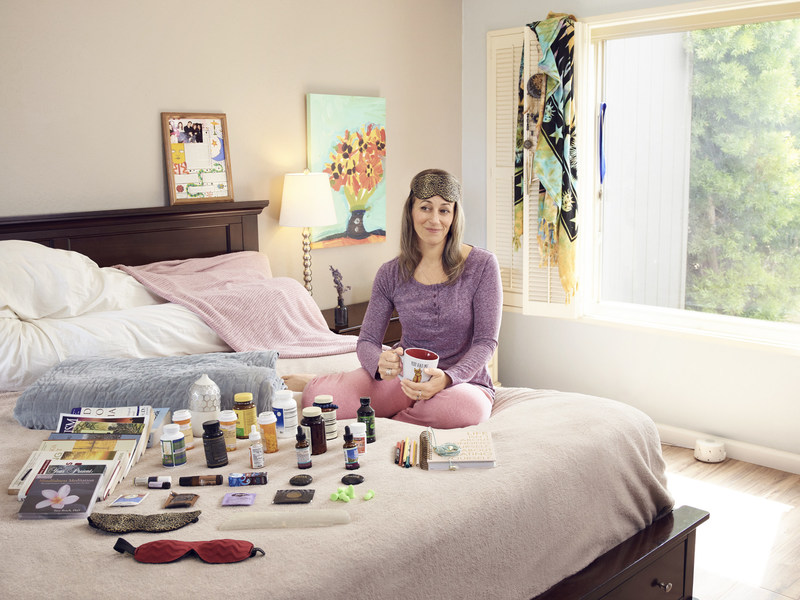 Ginger Soto, 43, surrounded by a variety of her sleep aids. According to survey findings, those who use sleep aids and supplements are less satisfied with their sleep than those who don't.