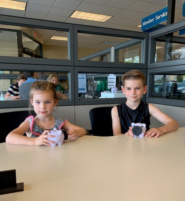 Two of OnPoint Community Credit Union's youngest members open OnPoint Savers Accounts at the credit union's branch in Lake Oswego, Oregon.