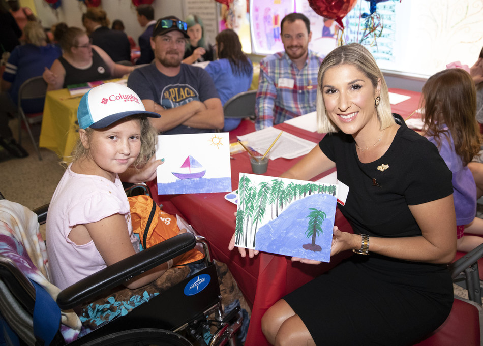 Brittany Hebert, Sky High Founder and CEO, displays artwork drawn by a St. Jude patient.