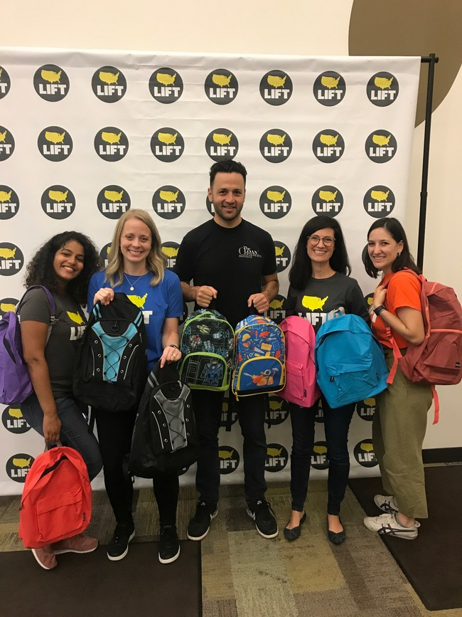 Jordan Tabach-Bank, founder of The Loan Companies, hands out backpacks filled with school supplies to kids while volunteering at the event.