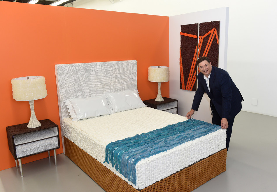 """Clem Bence, brand leader and vice president of operations for Howard Johnson by Wyndham, preps a candy-made re-creation of the brand's newly redesigned retro-cool guestroom at the pop-up event, """"HoJo's Sweet Escape,"""" on Thursday, Aug. 22, 2019 in New York. The event celebrates the brand's largest design-refresh in more than 25 years. (Diane Bondareff/AP Images for Howard Johnson by Wyndham)"""