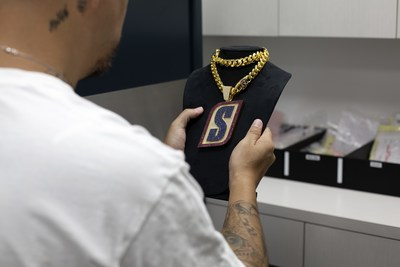 "The hand-crafted chain by Ben Baller features a pendant with more than 47 carats of brilliant-cut diamonds, blue sapphires and red rubies, highlighting the ""S"" from the iconic brand's logo.  Each week during the NFL season, the chain will be passed from one player to another player, who has not only shown hunger for more with a huge game or play on the field, but who is also driven to do more off the field."