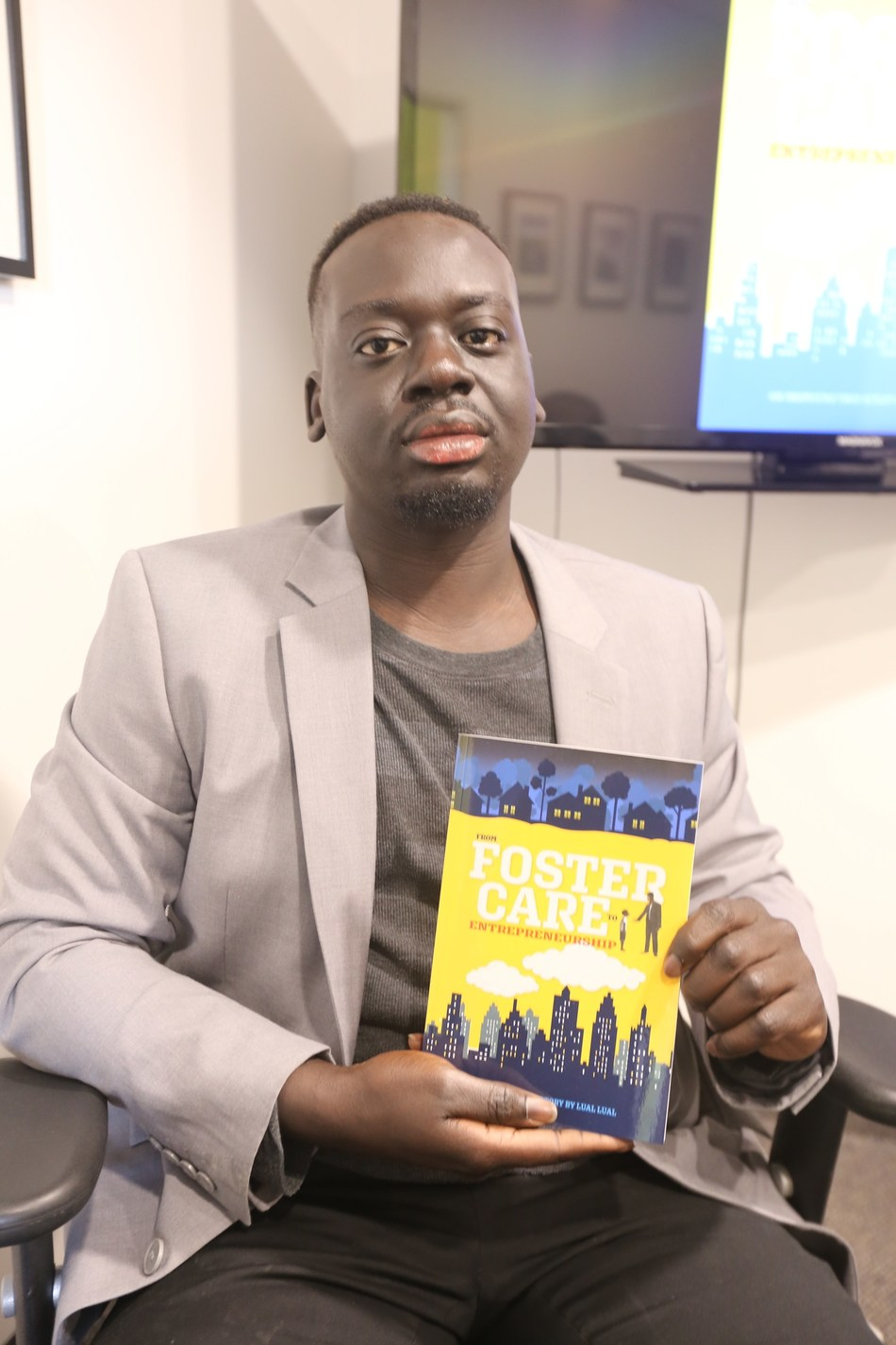 Lual Lual poses with his first published book. (CNW Group/From Foster Care To Entrepreneurship)