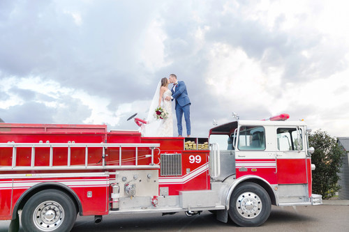 A newlywed couple standing atop a fire truck kissing
