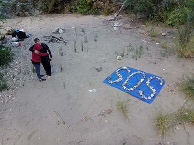 SOS Sign created by Whitson family after dropping their Nalgene water bottle, with SOS message, over the waterfall.