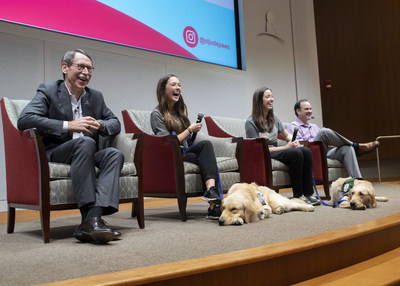 Left to right: St. Jude President and CEO James R. Downing, M.D., child life specialists Brittany Reed, Shandra Taylor, and child life program director Shawn Brasher, discuss the Paws at Play hospital dog program with staff. In front are Puggle and Huckleberry.