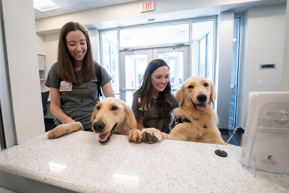 St. Jude Child Life specialists Shandra Taylor (left) and Brittany Reed will be the primary handlers for Huckleberry, a Golden Doodle, and Puggle, a Golden Retriever. The St. Jude Paws at Play hospital dogs will assist  in distracting pediatric patients from their illness, symptoms, pain and anxiety. They will also motivate and support patients through social interaction.