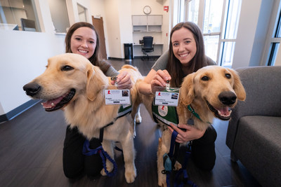 As the newest St. Jude employees, Puggle (left) and Huckleberry received their ID badges during orientation. They are accompanied in this photograph by their respective primary handlers, Child Life specialists Brittany Reed and Shandra Taylor.