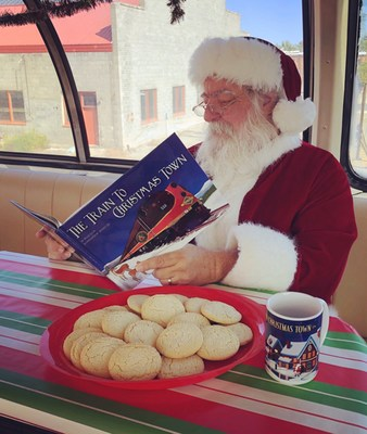Santa enjoying cookies and hot cocoa while reading the Train to Christmas Town book.