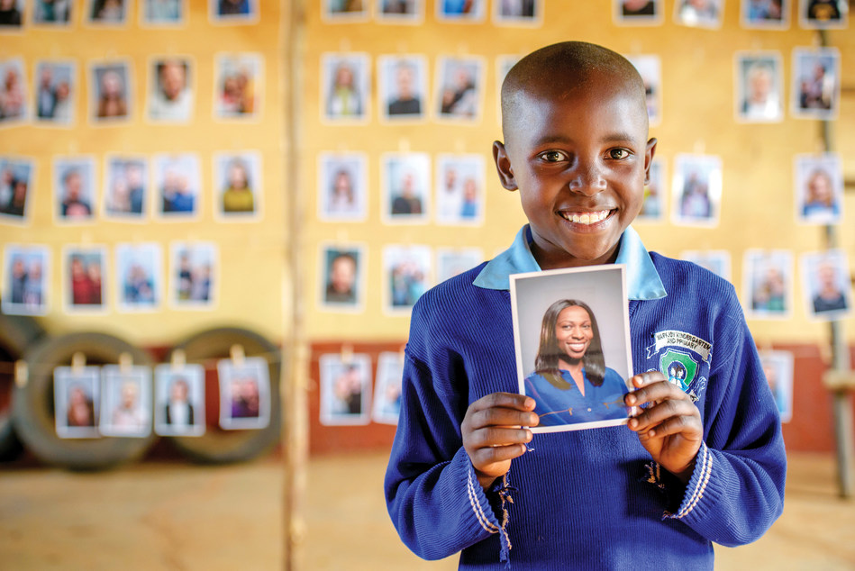 Portrait of Mary Nzioki holding a picture of her sponsor.