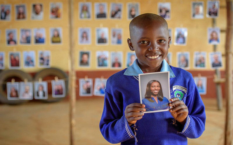 """Mary, 8, from Kenya, smiles as she holds the photo of the sponsor she chose. """"I picked the beautiful one,"""" she said. (CNW Group/World Vision Canada)"""